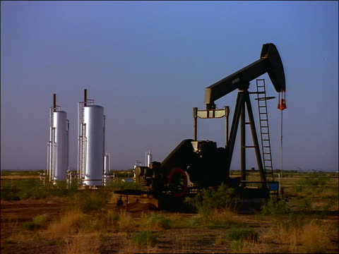 vídeos y material grabado en eventos de stock de slow moving oil pump with large metal containers or silos in background / texas - 1996