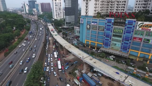 Slow moving traffic is seen under an elevated track for the Jakarta Mass Rapid Transit stands under construction in this aerial video taken in...
