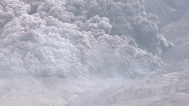 slow pan across large pyroclastic flow as it tears down the flanks of mt sinabung in indonesia during a powerful eruption - pyroklastischer strom stock-videos und b-roll-filmmaterial