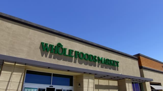 slow pan across signage with logo on the facade of the whole foods market grocery store in dublin california june 16 2017 - whole foods market stock videos and b-roll footage