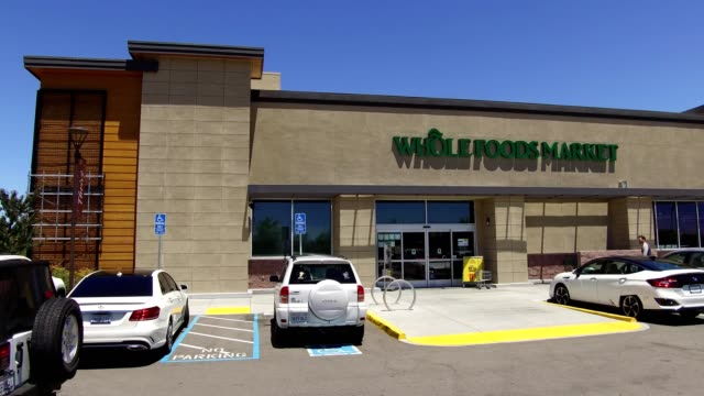 slow pan across the facade of the whole foods market store in dublin california as cars drive through the parking lot and shoppers walk near the... - whole foods market stock videos and b-roll footage
