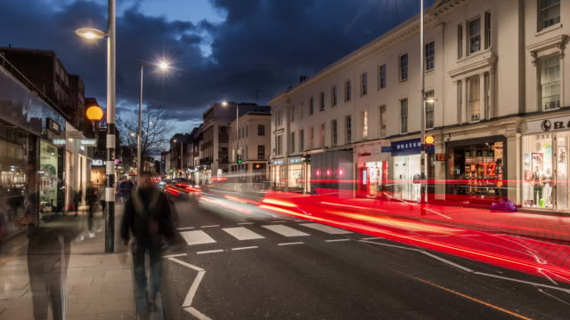vídeos de stock e filmes b-roll de a slow pan and tilt towards fast flowing traffic travelling along the kings road chelsea with pedestrians passing the streets famous shops in early evening dusk light - time lapse de trânsito