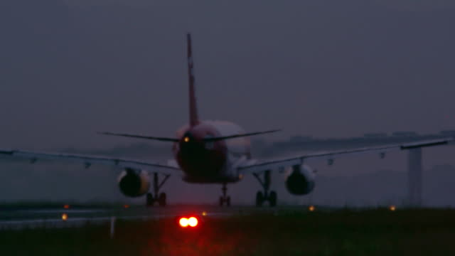 slow pan behind a commercial plane taking off at jacarepaguìá airport in brazil - panning stock videos & royalty-free footage