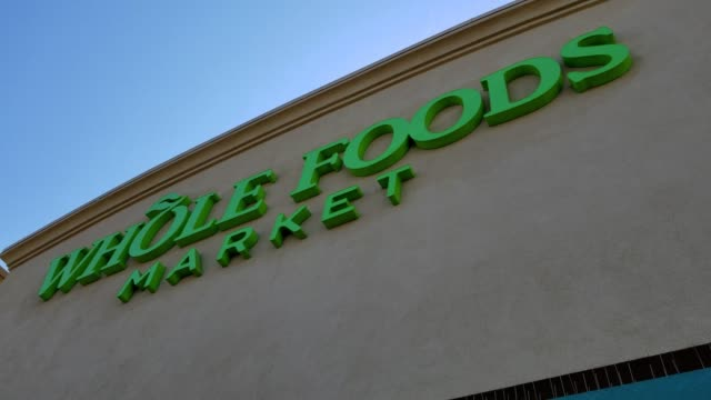 slow pan from signage for whole foods market to a temporary banner reading we're growing something good whole foods market and amazon announcing the... - whole foods market stock videos and b-roll footage