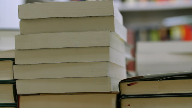 slow pan left of a pile of books on a table - wisdom stock videos & royalty-free footage