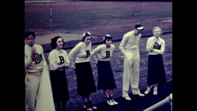 slow pan of cheerleaders lined up on side of field wearing varsity sweaters - cheerleader stock videos & royalty-free footage