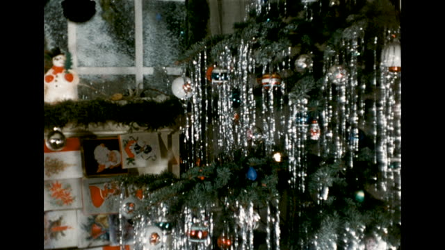 slow pan of christmas decorations, holiday cards, and a christmas tree with tinsel in a new jersey home. - ティンセル点の映像素材/bロール