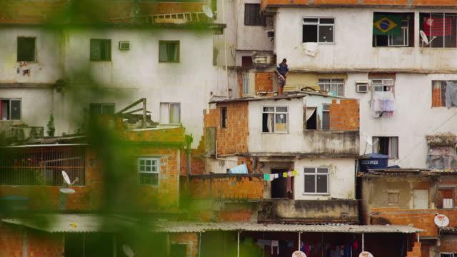 vídeos de stock, filmes e b-roll de rio de janeiro, brazil - june 23: slow pan of man on rooftop with kite rio de janeiro, 2013 - pipa brinquedo