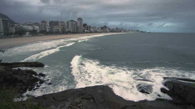vídeos de stock, filmes e b-roll de slow pan of rio skyline along the beach at dusk in rio de janeiro, brazil - fotografia de alta velocidade