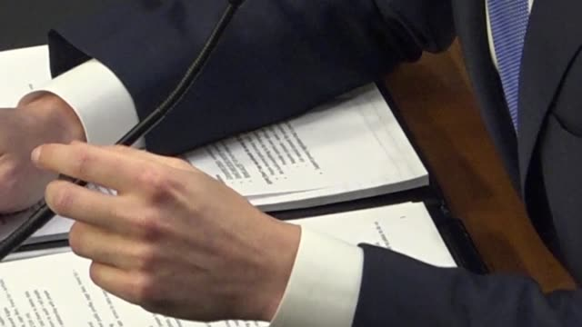 slow pan of the senate hearing room where facebook ceo mark zuckerberg testifies before a joint panel followed by a closeup of his hands over notes... - 法廷審問点の映像素材/bロール