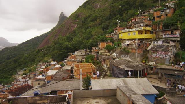 vídeos de stock e filmes b-roll de rio de janeiro, brazil - june 23: slow pan over a favela community and a soccer game - favela