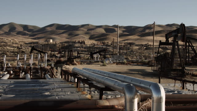 slow pan over oil field complex - pipeline stock videos and b-roll footage