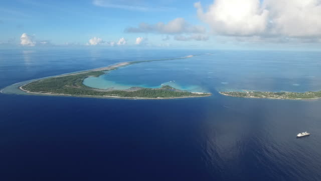 Slow pan right over Manihi Atoll, with cruise ship drifting outside the entrance