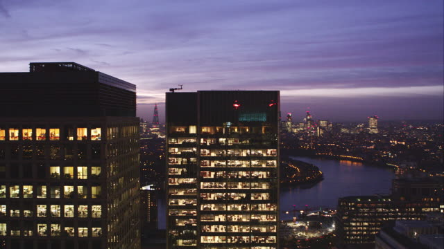 slow pan right shot of office block and cityscape at dusk - office block exterior stock-videos und b-roll-filmmaterial