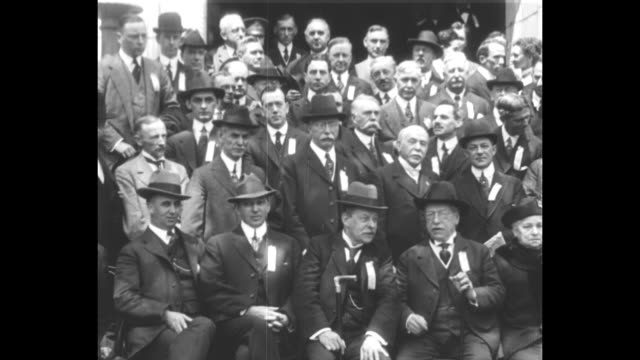 Slow pan shot of large seated group of labor leaders gathered to express support for US government in WWI / American Federation of Labor President...