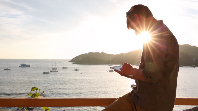 Slow pan up to man using digital tablet, on resort balcony above sea