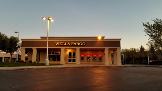 slow panning across facade of wells fargo bank branch location with atms visible at night in pleasanton california march 26 2018 - wells fargo stock videos and b-roll footage