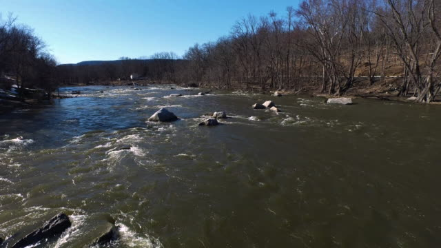 slow panning shot flying over a river water moving fast with rocks - new paltz stock videos and b-roll footage