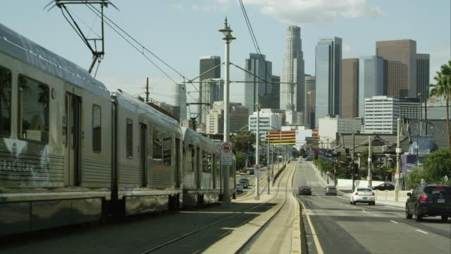 vidéos et rushes de slow panning shot of train driving down the street in los angeles. - ligne de tramway