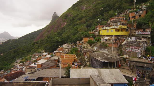 vídeos de stock e filmes b-roll de rio de janeiro, brazil - june 23: slow panning shot overlooking favela of rio showing a soccer game - favela
