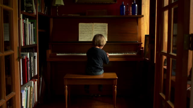 slow push in on boy playing piano. - silenzio video stock e b–roll