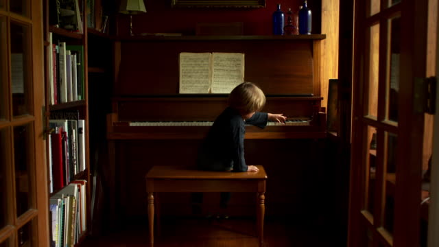 Slow push in on boy playing the scale on the piano.