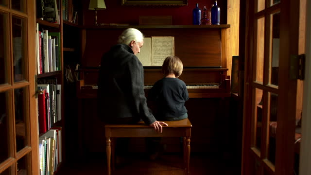 Slow push in on grandmother teaching grandson how to play the piano.