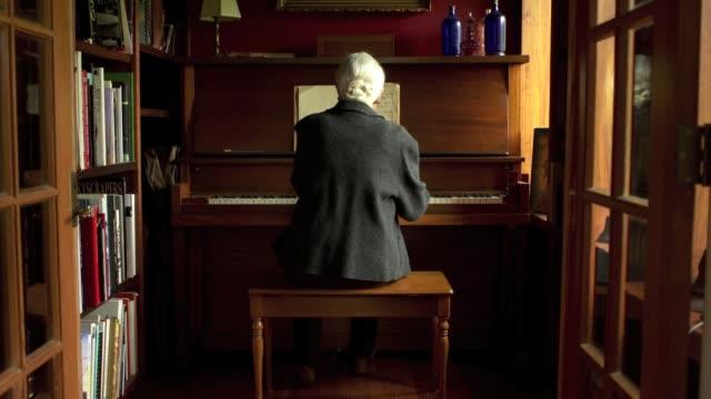 vídeos y material grabado en eventos de stock de slow push in on woman playing piano. - piano