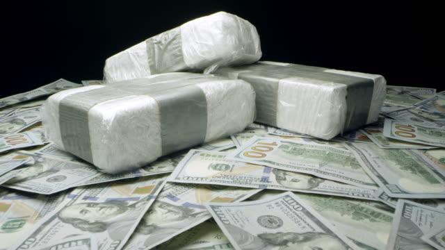 slow push in towards bricks of drugs on money - cocaina video stock e b–roll