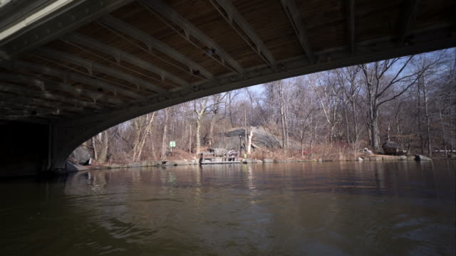 Slow reveal from underneath bridge of couple enjoying view of Central Park lake