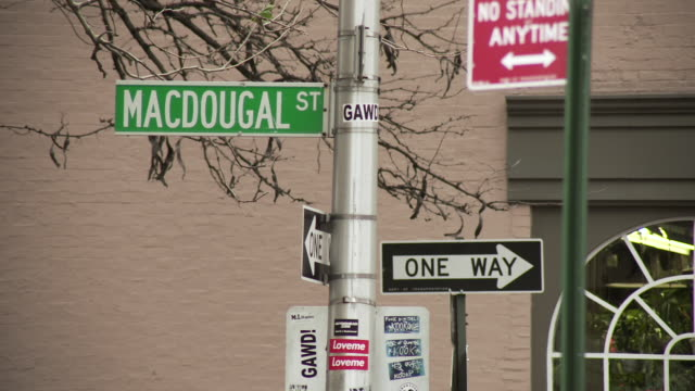Slow reveal of the street sign at MacDougal street in manhattan as the tops of cars pass quickly in front