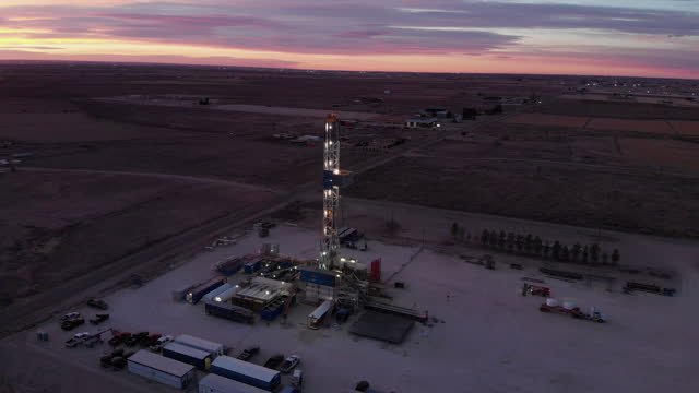 slow right to left parallax drone shot fracking oil and gas drill rig at dawn or dusk in west texas or southeast new mexico region of the southern united states oil field near carlsbad - drill stock videos & royalty-free footage