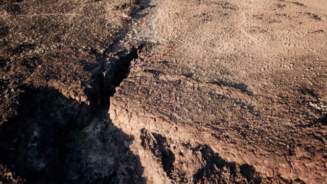 Slow Rise Over Edge of Volcanic Cliff Face Reveal Distant Cinder Cone