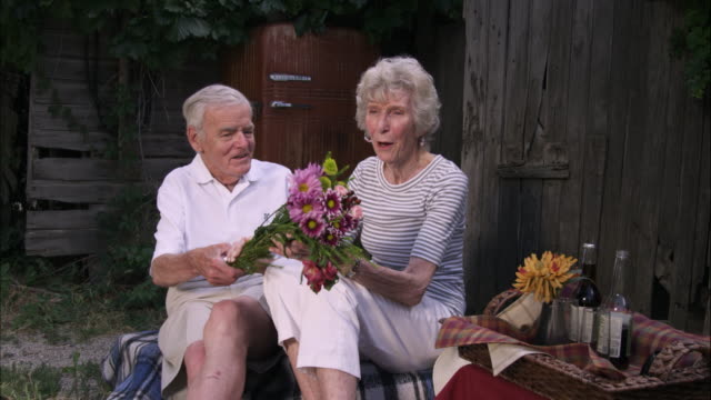 slow static shot of a romantic old man surprising his wife a bouquet of flowers - bunch of flowers stock videos & royalty-free footage