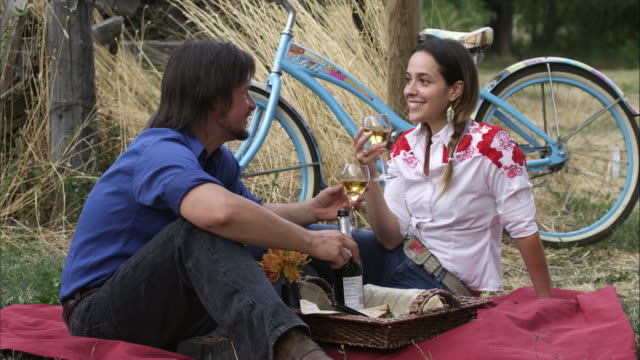 Slow static shot of a young couple having an outdoor picnic