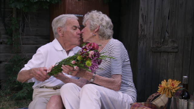 Slow static shot of an elderly man surprising his wife with a bouquet of flowers