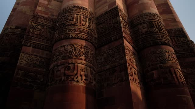 "slow tilt down to closeup view of facade surfaces that are elaborately decorated with inscriptions and geometric patterns of the qutab minar tower minaret or ""victory tower"", part of the qutb complex during 2020 - minareto video stock e b–roll"