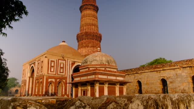 "slow tilt down to view of the majestic qutab minar tower minaret or ""victory tower"" along with alai darwaza is a main gateway from southern side of the quwwat-ul-islam mosque in 2020 with no tourists or visitors - minareto video stock e b–roll"