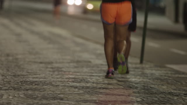 slow tilt shot of runner shoes and orange shorts in rio. - running shorts stock videos & royalty-free footage