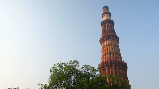 "slow tilt up to view of the majestic qutab minar tower minaret or ""victory tower"" that forms part of the qutb complex during 2020 with no tourists - minareto video stock e b–roll"
