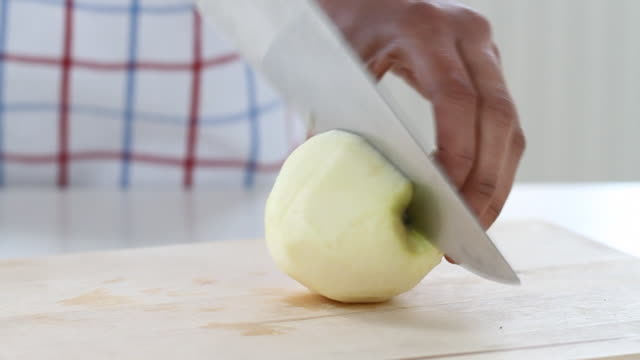 Slow track across mixed race hands chopping an apple