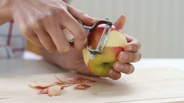stockvideo's en b-roll-footage met slow track across mixed race hands peeling an apple - schil
