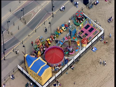 slow track backwards over fairground on beach scarborough - scarborough inghliterra video stock e b–roll