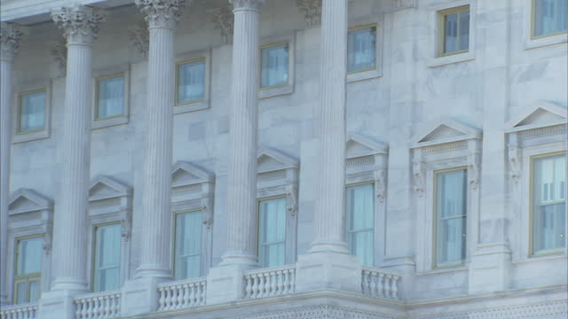 slow track into windows and columns of the us capitol building - pediment stock videos & royalty-free footage