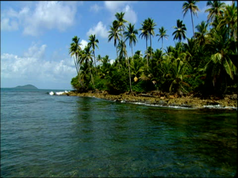Slow track over calm blue sea idyllic palm tree lined coast blue sky with clouds Panama