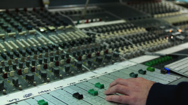 Slow tracking shot of a sound mixing desk in use