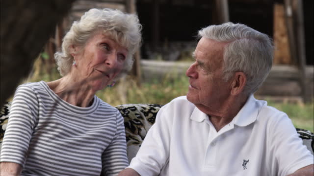 Slow tracking shot of elderly couple having an animated conversation