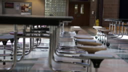 Slow Tracking Shot Of Empty Chairs In School Cafeteria