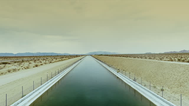 slow tracking through concrete canal transporting colorado river aqueduct water through open desert - 1941 stock videos & royalty-free footage