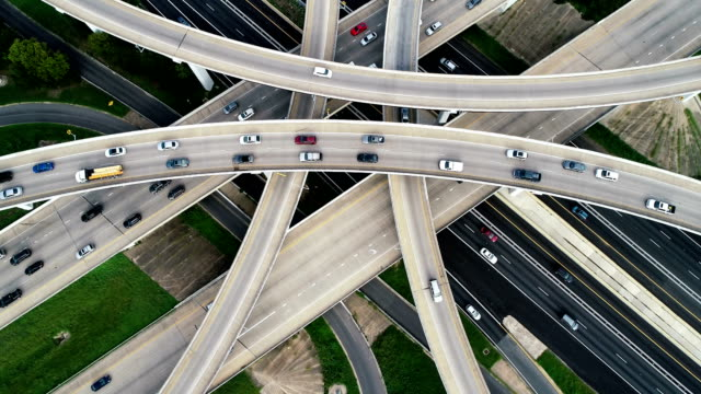 slow turning as traffic drives across futuristic transportation highway and modern infrastructure - texas stock videos & royalty-free footage